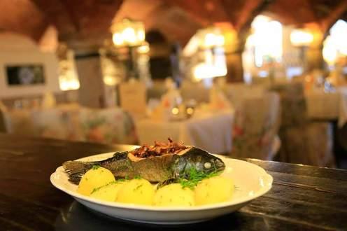 Vollkost: mit Speckzwiebeln und Pfifferlingen gefüllte Bayerwaldforelle, serviert im Romantikhotel Gut Schmelmerhof.