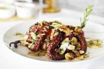 """Der Oktopus """"à lagareiro"""" wird mit Olivenöl und hauchdünn geschnittenen Knoblauchscheiben verfeinert. Die Kartoffel scheint er selbst verschlingen zu wollen"""