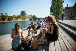 Sonnendeck: Picknick mit Seine-Blick auf den Holzstufen vor dem Musée d'Orsay. Pariser und Touristen genießen die Ufer-Oasen mitten in der Stadt.
