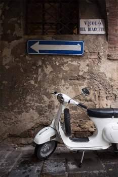 Vespapause: Die Primavera 125 aus dem Jahr 1974 parkt unter einem Torbogen in dem mittelalterlichen Städtchen Montalcino. Veteranen unter sich.