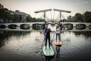 Stehplatz in Amsterdam: Die Boards, die hier vor der Mageren Brücke dahingleiten, sind 3,50 m lang. Toruguide Morene Dekker (re.) hat den Trend Stand-up-Paddle nach Amsterdam gebracht. Sie führt Autor Janek Schmidt durch die Stadt.
