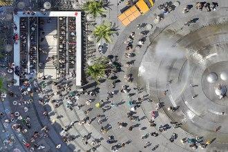 Platz da: Der Karlsplatz, auch Stachus genannt. In der rechten Bildhälfte ist der Springbrunnen zu sehen, links der Eingang zur U-Bahn.
